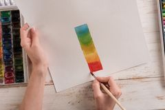 Artist painting colorful stripes with brush on white paper Stock Image