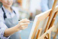 Artist Painting on Easel. Close up of unrecognizable artist painting picture on easel enjoying work in art studio, copy space stock photos