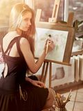 Artist painting on easel in studio. Girl paints with brush. Artist painting on easel and palette in studio. Authentic girl paints with oil brush morning Royalty Free Stock Image