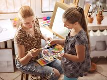 Artist painting on easel in studio. Authentic children paints . Stock Photography