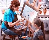 Artist painting easel in studio. Authentic grandmother and kids. Artist painting easel in studio. Authentic grandmother and kids girl paints with palette stock photo
