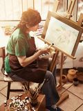 Artist painting easel in studio. Authentic senior woman. Artist painting easel in studio. Authentic senior woman has small home own business paints with brush stock photography