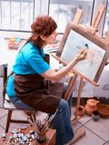 Artist painting easel in studio. Authentic senior woman. royalty free stock photo
