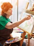 Artist painting easel in studio. Authentic senior woman. stock photos