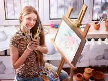 Artist painting on easel in studio. Girl paints with brush. stock photography