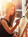 Artist painting on easel in studio. Girl paints with brush. Artist painting on easel in studio. Girl paints with brush in morning sunlight dawn light toning stock photos