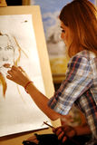 Artist painting on easel in studio. Girl paints portrait of woman with brush. Stock Photo