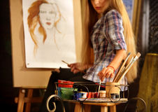 Artist painting on easel in studio. Girl paints portrait of woman with brush. Stock Photography