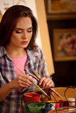 Artist painting on easel in studio. Girl paints portrait of woman with brush. Royalty Free Stock Photography