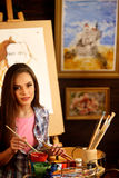 Artist painting on easel in studio. Girl paints portrait of woman with brush. Royalty Free Stock Photo