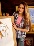 Artist painting on easel in studio. Girl paints portrait of woman with brush. Royalty Free Stock Image