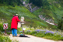 Artist Painting en Plein Air. Senior male artist painting en plein air with his easel, palette, and his canvas with a partially finished oil painting of the Stock Photo