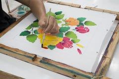 Artist painting flower on fabric. Stock Image