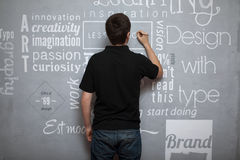 Artist painting fonts. An artist painting multiple fonts on a gray wall Royalty Free Stock Photos