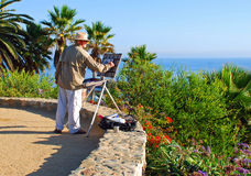 An artist painting in Heisler Park, Laguna Beach.C Royalty Free Stock Image