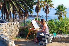 An artist painting in Heisler Park, Laguna Beach, CA. The image shows an artist painting a seascape in Heisler Park, Laguna Beach.California. Picturesque and royalty free stock photo