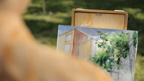 Artist painting a house and a tree from nature. Plein air. Artist painting a house and a tree from nature. The artist paints watercolors on canvas. Plein air stock footage