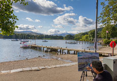 Artist painting the lake and a pier in Ambleside in Lake Windremere Royalty Free Stock Photography