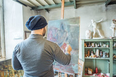 An artist painting a masterpiece at his studio.  royalty free stock photo