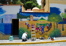 Artist painting outdoor mural. Artist on ladder painting outdoor mural in Ajijic, Mexico Royalty Free Stock Photography