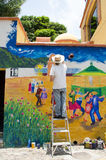 Artist painting outdoor mural. Artist on ladder painting outdoor mural in Ajijic, Mexico Stock Image