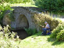 Artist painting by old stone bridge. An artist painting outdoor scenery by old stone bridge at Malmsmead in Devon, England Royalty Free Stock Images