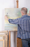 An artist painting with a palette knife in studio Royalty Free Stock Photography
