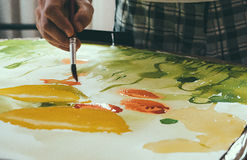 Artist painting picture on canvas with watercolours.  royalty free stock image