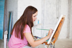 Artist painting picture on canvas whith watercolours. In her white studio stock image