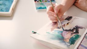 Artist painting sketchbook hand watercolor artwork. Artist painting in sketchbook. Watercolor artwork in process. Delicate woman hand closeup applying blue paint stock footage