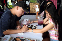 An artist are painting some nice tatto to a young girl. In a flea market, sai gon, viet nam Stock Photo