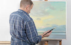 An artist painting in studio Stock Image