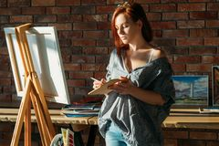 Artist painting studio workspace easel mix palette. Artist painting. Studio workspace. Redhead female with easel mixing colors on wooden palette stock photography