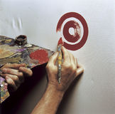 Artist painting a target. Artist's hand with a brush painting a target Royalty Free Stock Photo