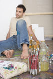 Artist With Painting Tools Sitting On Studio Floor Royalty Free Stock Image