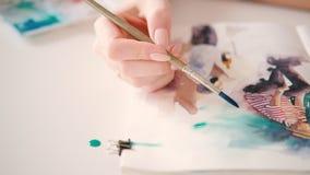 Artist painting watercolor artwork hand sketchbook. Artist painting creating watercolor artwork. Open sketchbook. Delicate woman hand closeup applying blue paint stock footage
