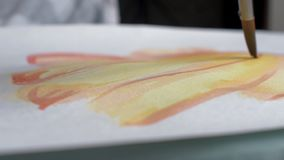 Artist painting watercolor paints on wet paper stock footage