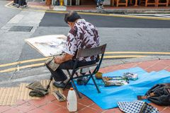 Artist painting watercolour. Singapore - 22nd December 2018: Artist painting watercolour on Arab Street. This is in the Kampong Glam area royalty free stock photos