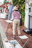 Artist painting watercolour. Singapore - 22nd December 2018: Artist painting watercolour on Arab Street. This is in the Kampong Glam area stock images