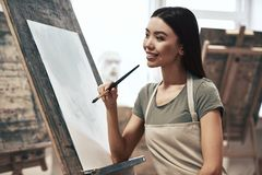 Artist painting. A young beautiful woman is a painting artist while working in a studio stock photography