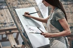 Artist painting. A young beautiful woman is a painting artist while working in a studio stock image