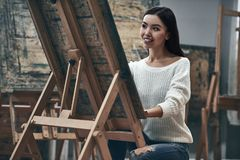 Artist painting. A young beautiful woman is a painting artist while working in a studio royalty free stock images