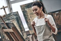 Artist painting. A young beautiful woman is a painting artist while working in a studio royalty free stock photo