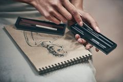 Artist painting. Young beautiful woman painting artist while working in studio, hands close-up royalty free stock photo