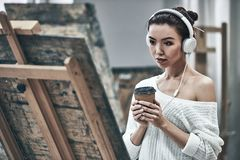 Artist painting. Young beautiful woman painting artist while working in studio, listening to music in headphones royalty free stock image