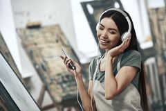 Artist painting. Young beautiful woman painting artist while working in studio, listening to music in headphones royalty free stock photography