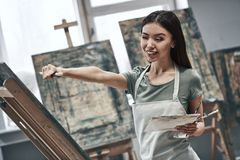 Artist painting. Young beautiful woman painting artist while working in a studio, smiling to the camera stock photography