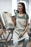 Artist painting. Young beautiful woman painting artist while working in a studio, smiling to the camera stock photos