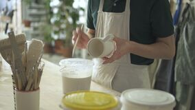 Artist paints a brush with white paint on a ceramic cup. stock video footage