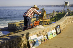 Artist Paints. La Jolla, California. A male artists paints palm trees in oils on the coastal bluff overlooking the Pacific Ocean in La Jolla, California, while stock photos